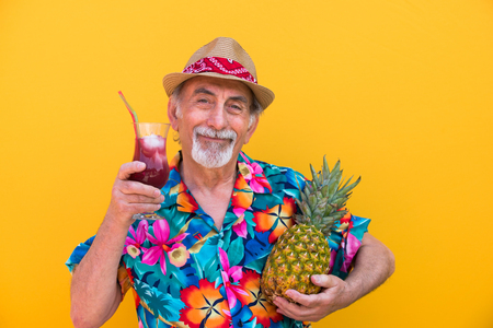 Funny and extravagant senior man posing on colored background - Youthful old man in the sixties having fun and partying Standard-Bild