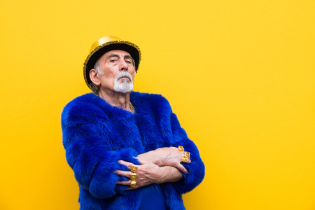 Funny and extravagant senior man posing on colored background - Youthful old man in the sixties having fun and partying Foto de archivo - 111586741