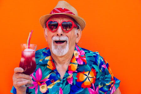 Funny and extravagant senior man posing on colored background - Youthful old man in the sixties having fun and partying Archivio Fotografico