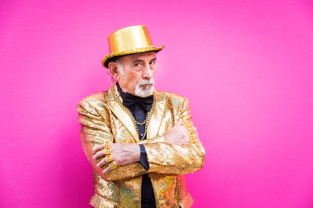 Funny and extravagant senior man posing on colored background - Youthful old man in the sixties having fun and partying Stock fotó