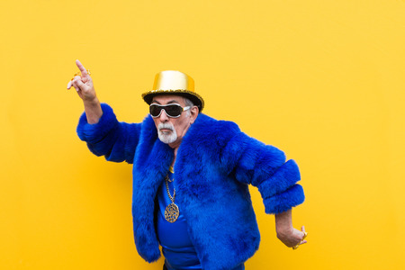 Lustiger und extravaganter älterer Mann, der auf farbigem Hintergrund posiert - Jugendlicher alter Mann in den sechziger Jahren, der Spaß hat und feiert