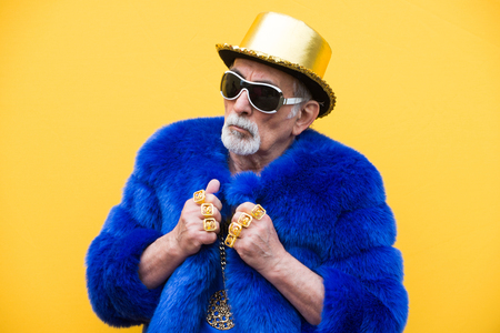 Funny and extravagant senior man posing on colored background - Youthful old man in the sixties having fun and partying Stockfoto - 111586903