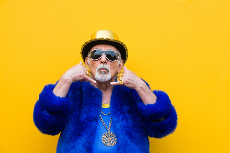 Funny and extravagant senior man posing on colored background - Youthful old man in the sixties having fun and partying Imagens