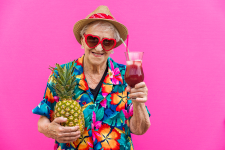 Funny and extravagant senior woman posing on colored background - Youthful old woman in the sixties having fun and partying Stock Photo
