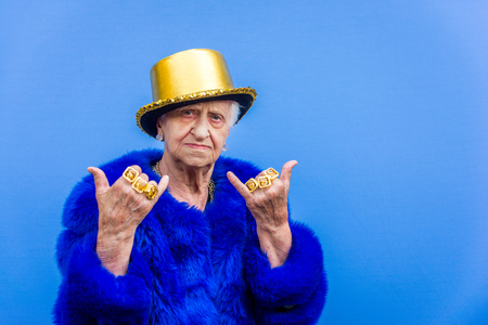 Funny and extravagant senior woman posing on colored background - Youthful old woman in the sixties having fun and partying Imagens