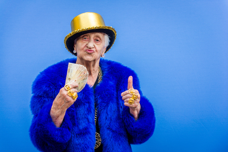 Funny and extravagant senior woman posing on colored background - Youthful old woman in the sixties having fun and partying Фото со стока