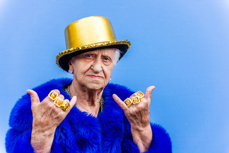 Funny and extravagant senior woman posing on colored background - Youthful old woman in the sixties having fun and partying Stock Photo - 111481561
