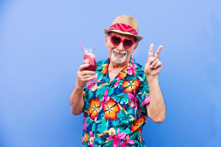 색색의 배경 위에 포즈를 취하는 재미있고 사치스러운 노인 - 재미와 파티를 즐기는 60대 노인 스톡 콘텐츠