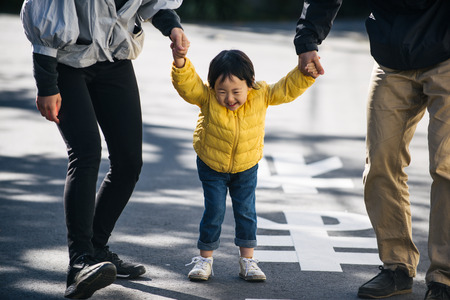 Happy and playful japanese family with small cute daughter having fun outdoors