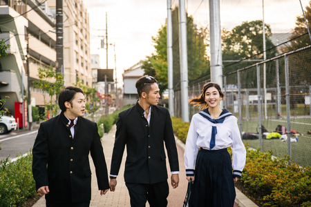 Young japanese students with school uniform bonding outdoors - Group of asian teenagers having fun