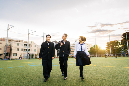 Yung japanese students with school uniform bonding outdoors - Group of asian teenagers having fun