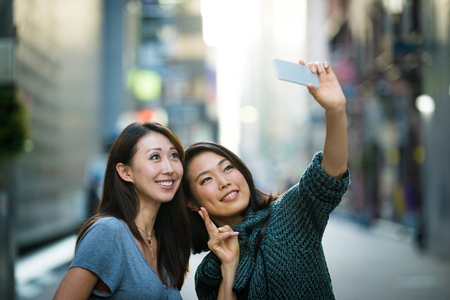 Two girlfriends meeting outdoors and having fun - Japanese people bonding on Tokyo streets