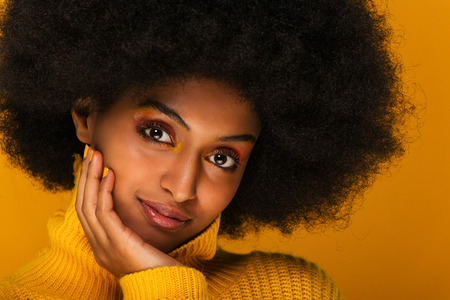 Portrait of pretty afro american woman in a studio for a beauty session - Beautiful girl posing on colored background