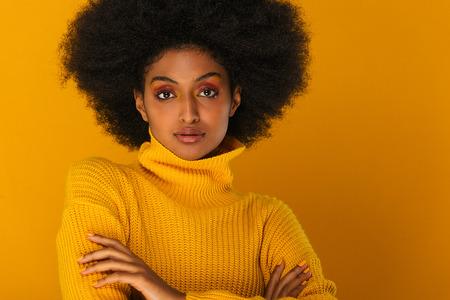 Portrait de jolie femme afro-américaine dans un studio pour une séance de beauté - Belle fille posant sur fond coloré