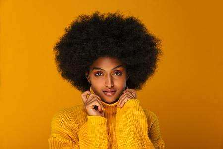 Portret van een mooie Afro-Amerikaanse vrouw in een studio voor een schoonheidssessie - Mooi meisje dat zich voordeed op een gekleurde achtergrond