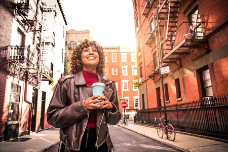 Heureuse femme afro-américaine souriante. Belle jeune femme marchant et s'amusant à New York
