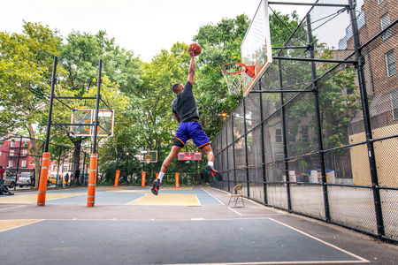 Afro-american basketball player training on a court in New York - Sportive man playing basket outdoors 免版税图像