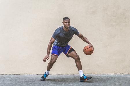 Joueur de basket-ball afro-américain s'entraînant sur un terrain à New York - Homme sportif jouant au panier à l'extérieur Banque d'images