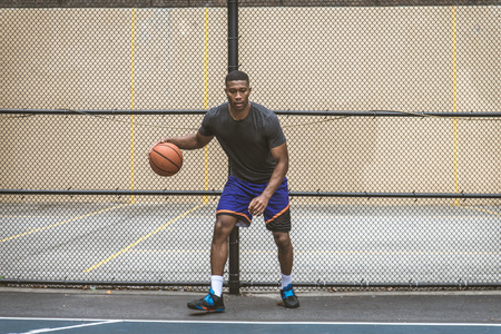 Afro-american basketball player training on a court in New York - Sportive man playing basket outdoors Standard-Bild
