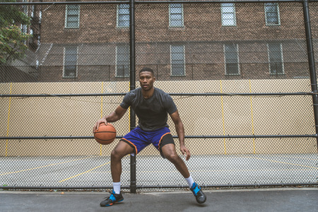Afro-american basketball player training on a court in New York - Sportive man playing basket outdoors 版權商用圖片