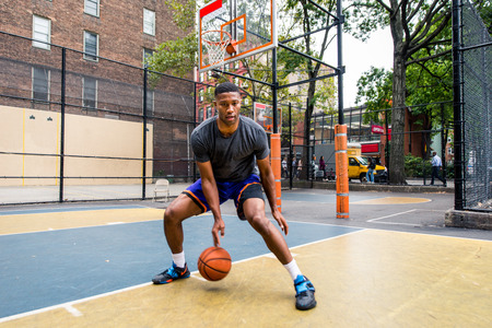 Afro-american basketball player training on a court in New York - Sportive man playing basket outdoors Banco de Imagens