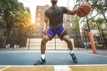 Afro-american basketball player training on a court in New York - Sportive man playing basket outdoors Stock Photo