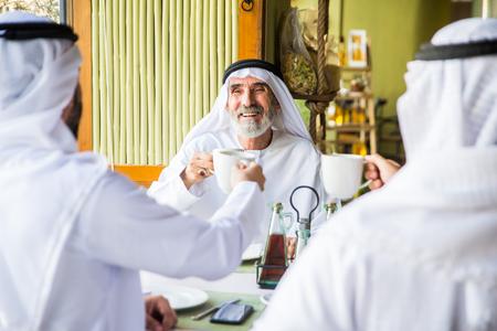 Group of middle eastern men wearing kandora bonding in a cafè restaurant in Dubai Stock Photo