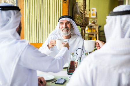 Group of middle eastern men wearing kandora bonding in a cafè restaurant in Dubai 版權商用圖片