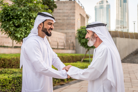 Group of arabian businessmen with kandura meeting outdoors in UAE - Middle-eastern men in Dubai Stock Photo - 117531219