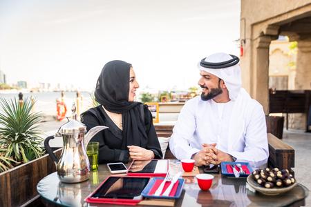 Arabisches Paar mit traditioneller Emirates-Kleidung im Freien - Glückliches Paar aus dem Nahen Osten, das Spaß hat