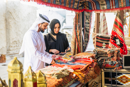 Arabian couple with traditional emirates dress dating outdoors - Happy middle-eastern couple having fun