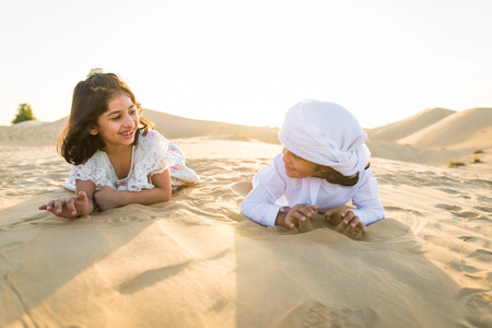 Arabian family with kids having fun in the desert - Parents and children celebrating holiday in the Dubai desrt Stock Photo - 119767404