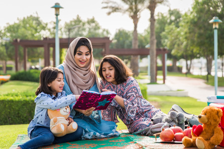 Happy arabian family having fun in Dubai - Mom together with her daughters in a park