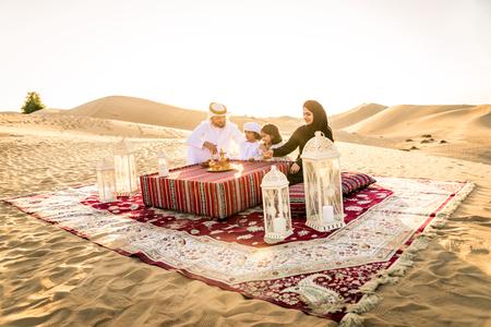 Famiglia araba con bambini che si divertono nel deserto - Genitori e bambini che festeggiano le vacanze nel deserto di Dubai Archivio Fotografico