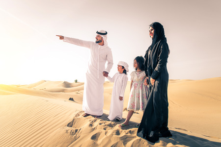 Arabian family with kids having fun in the desert - Parents and children celebrating holiday in the Dubai desert Imagens