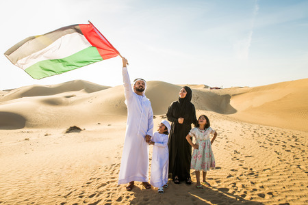 Arabian family with kids having fun in the desert - Parents and children celebrating holiday in the Dubai desert Фото со стока