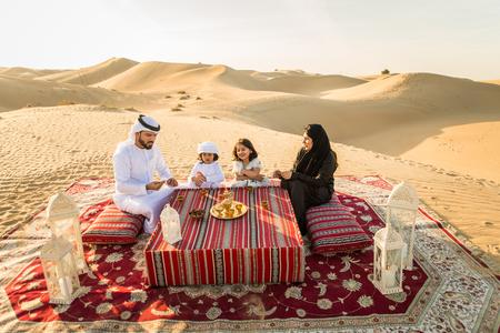 Arabian family with kids having fun in the desert - Parents and children celebrating holiday in the Dubai desert Stock Photo