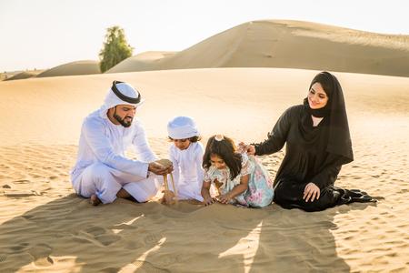 Arabian family with kids having fun in the desert - Parents and children celebrating holiday in the Dubai desert Imagens