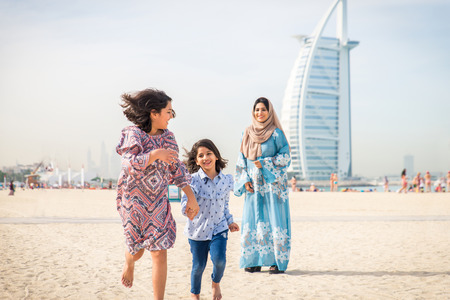 Happy arabian family having fun in Dubai - Mom together with her daughters on the beach