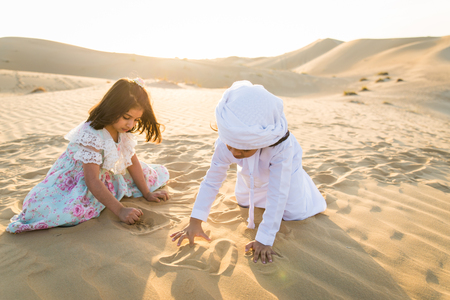 Arabian family with kids having fun in the desert - Parents and children celebrating holiday in the Dubai desrt