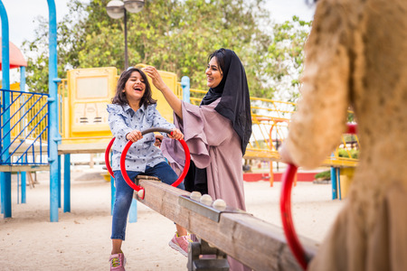 Happy arabian family having fun in Dubai - Mom together with her daughters in park play area