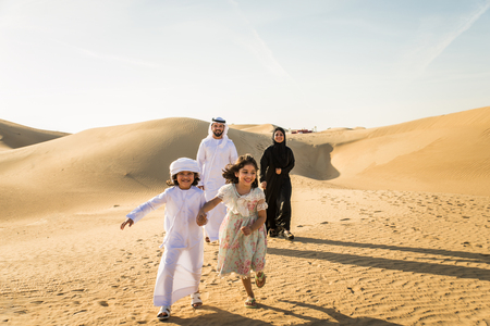 Arabian family with kids having fun in the desert - Parents and children celebrating holiday in the Dubai desrt Stock Photo
