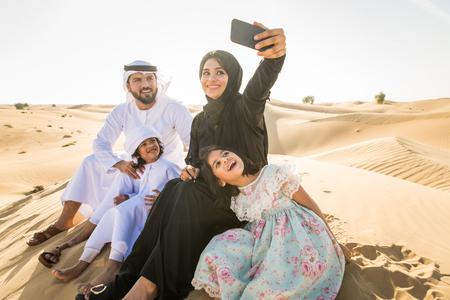 Arabian family with kids having fun in the desert - Parents and children celebrating holiday in the Dubai desert