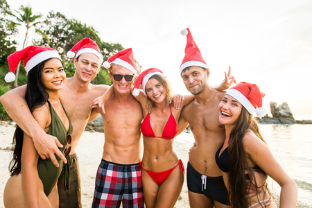 Group of happy friends on a tropical island having fun - Young adults playing together on the beach, summer vacation on a beautiful beach Stock Photo
