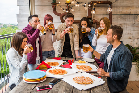 Group of happy friends bonding at home - Young adults having lunch and spending time together on a rooftop terrace, eating pizza and snacks