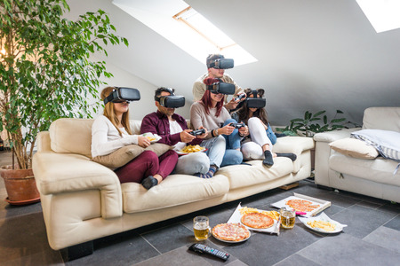 Group of happy friends bonding at home - Young adults having party and playing with videogames and vr helmets