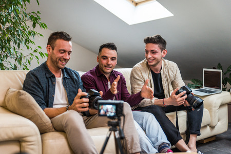 Group of social network influencers filming a vlog at home, talking and reviewing a product