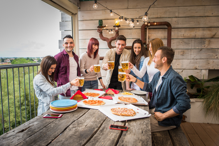 Grupo de amigos felices que se unen en casa - Adultos jóvenes almorzando y pasando tiempo juntos en una terraza en la azotea, comiendo pizza y bocadillos