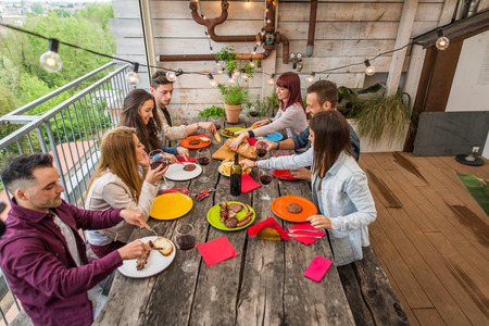 Group of happy friends bonding at home - Young adults having lunch and spending time together on a rooftop balcony, cooking meat on barbecue