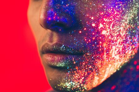 Handsome boy dancing at the rave party with fluorescent paintings on his face Stock Photo